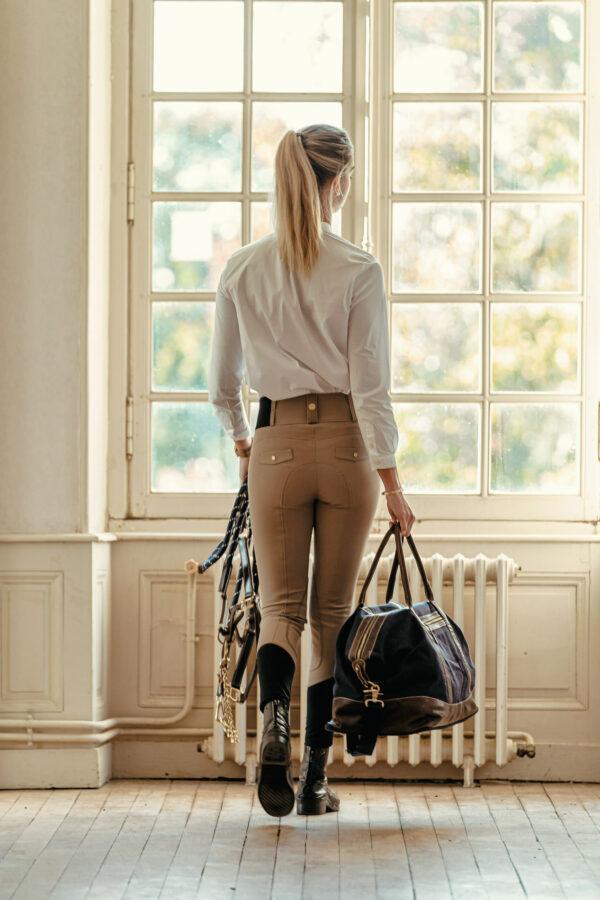 A Tiss B - femme - pantalon romy - selle de cheval - chemisier blanc - pré - champs - soleil - femme qui regarde par la fenêtre - sac