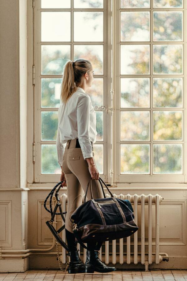 A Tiss B - femme - pantalon beige - pantalon romy - fenêtre - sac - licol - femme qui regarde part la fenêtre - Haras national du Lion d'Angers